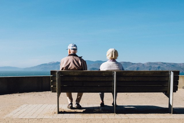 Elderly couple sitting on a bench, looking at a mountain landscape.