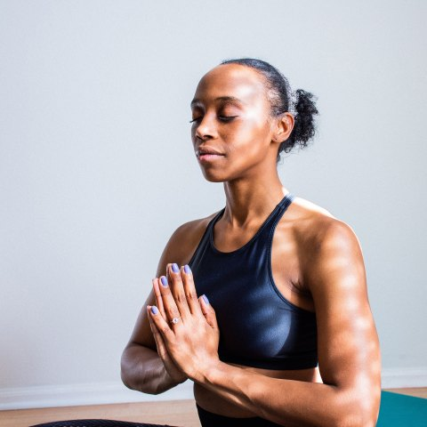 A woman in a yoga pose with her hands joined together and her eyes closed.