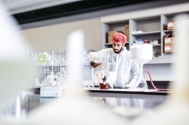 A MetaDerm employee working with chemicals in a lab environment.