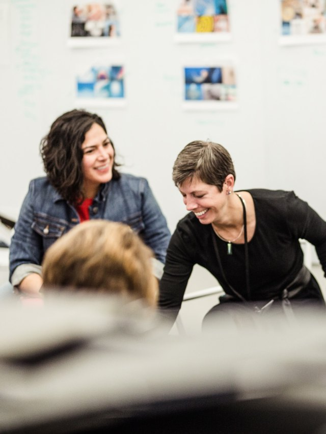 Two women sitting in a meeting room among other people, exchanging ideas with a smile.