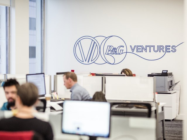 An open office with people working on computers and a large P&G Ventures logo is drawn onto one of the walls.